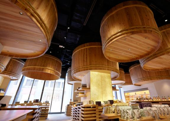 Butoaie mari din lemn sunt suspendate deasupra clientilor in acest magazin de sos de soia
